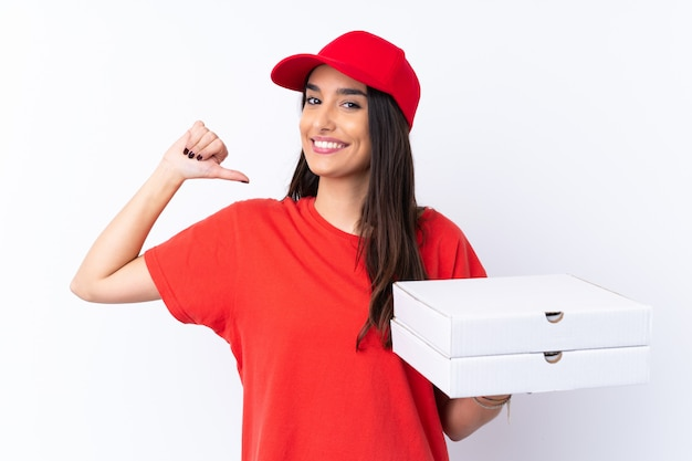 Pizza delivery woman holding a pizza over white wall proud and self-satisfied