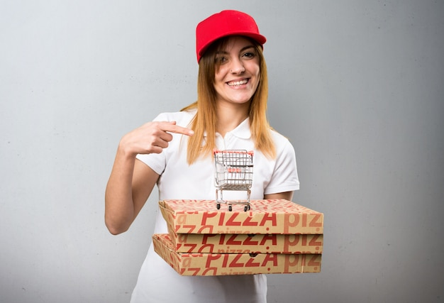 Pizza delivery woman holding a supermarket cart toy on textured background