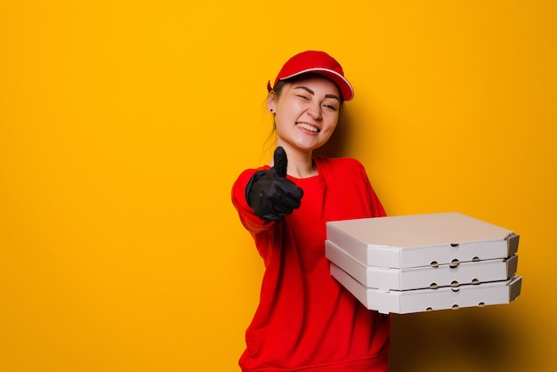 노란색 벽에 고립 된 세 개의 상자를 들고 피자 배달 여자