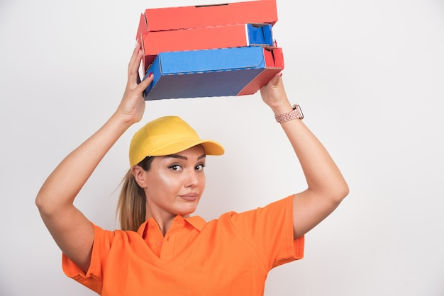 白い背景の上の彼女の頭にピザの箱を置くピザ配達の女性。