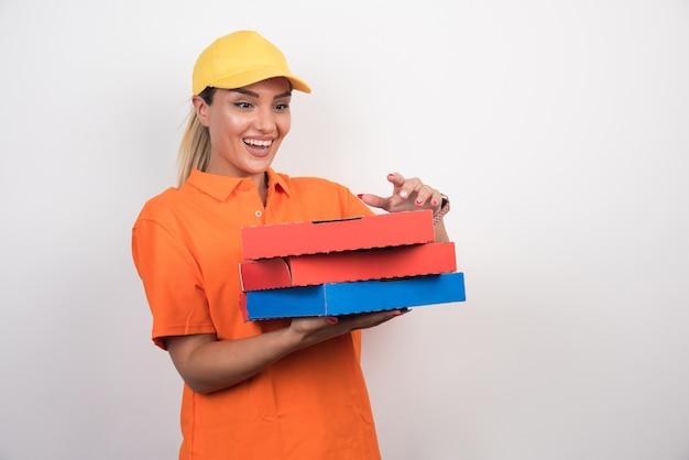 Donna di consegna pizza cercando di aprire la scatola della pizza con la faccia felice su uno spazio bianco