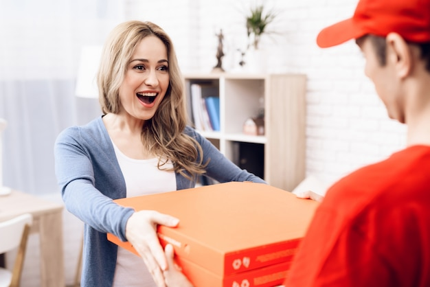 Pizza deliveryman gives pizza box smiling girl.
