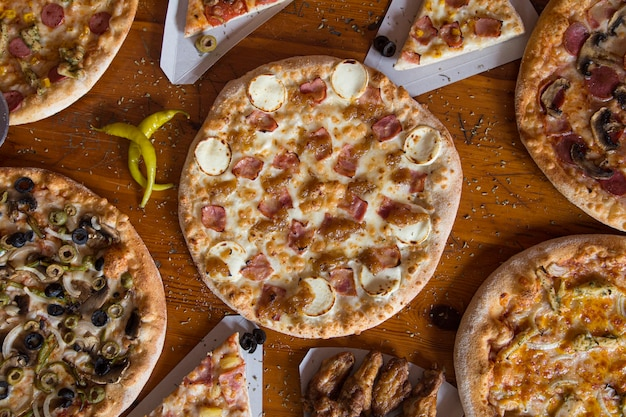 Pizza dinner. flat of various kinds of italian pizza on rustic wooden table, top view