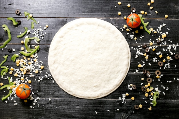 Pizza dough next to cheese sprinkles olive corn tomato and bell pepper on black wooden background