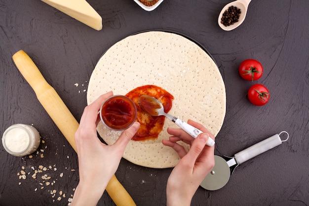 ピザ生地、ケチャップを手で生地に塗っています。 Premium写真