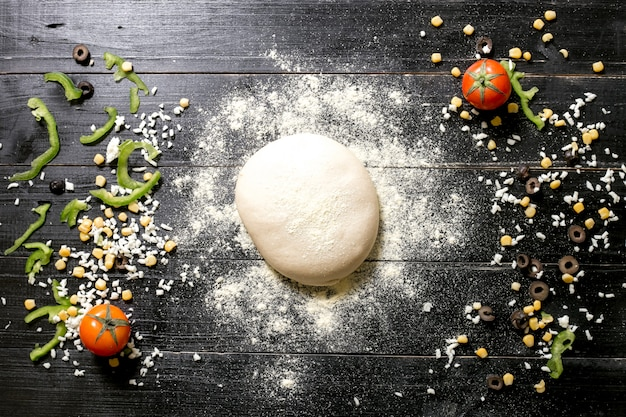 チーズの横に小麦粉を振りかけたピザ生地にオリーブコーントマトピーマンを振りかける