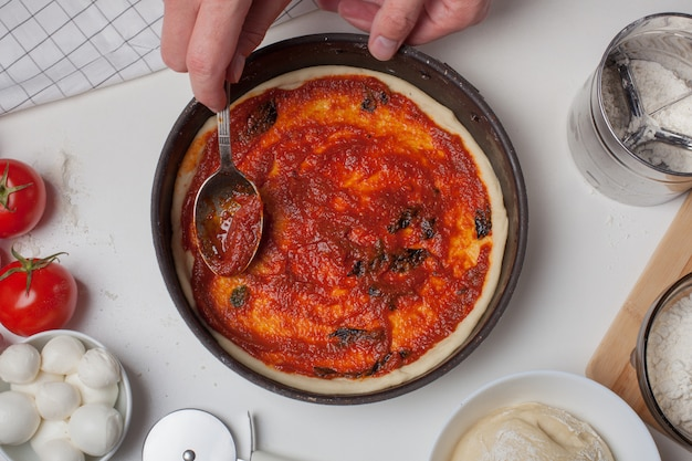 Pizza dough with ingredients and tomato sauce.