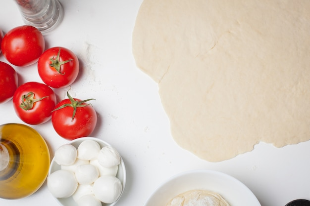 Pizza dough with ingredients.