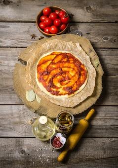 トマトソース、トマト、ピザ用麺棒の材料が入ったピザ生地。