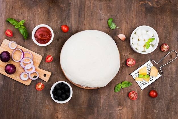 Pizza dough on wooden background