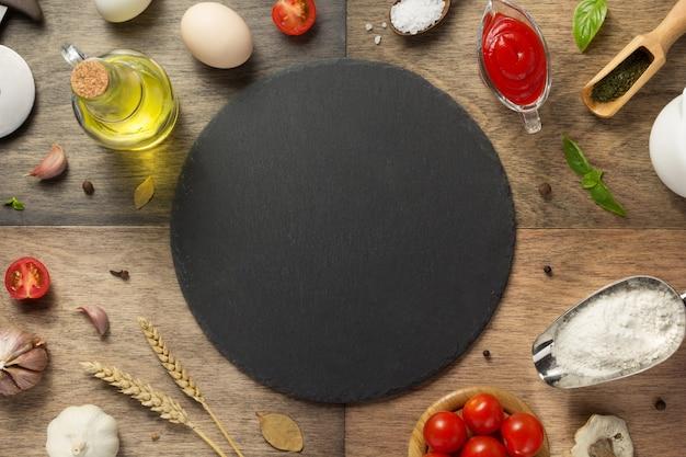 木製のテーブル、上面図でピザ食材とスレート石まな板
