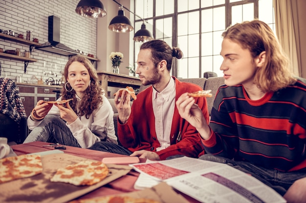 ランチにピザ。ランチにおいしいピザを食べる3人の若いアクティブなミュージシャンの会社