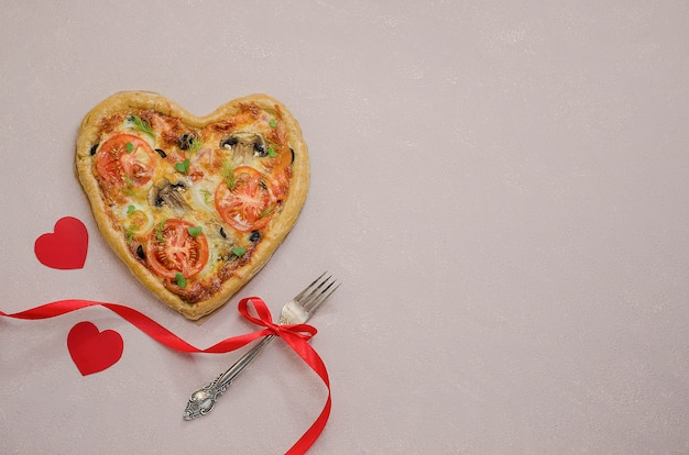 Pizza in the form of a heart on a beige table with red hearts with a fork with a red ribbon. order pizza for a romantic dinner on valentine's day. love.