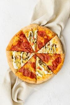 Пицца из разных кусочков на льняном полотенце. вертикальная ориентация, вид сверху, плоская планировка.