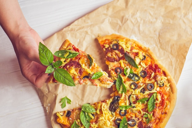 Pizza and hand close up over white background