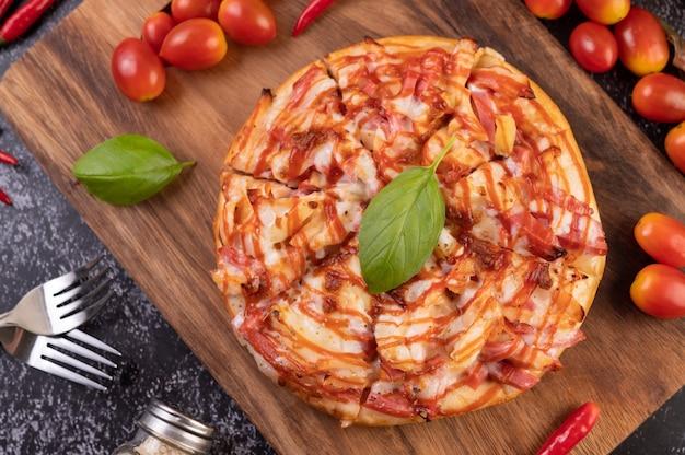 Пицца в деревянном подносе с помидорами чили и базиликом.