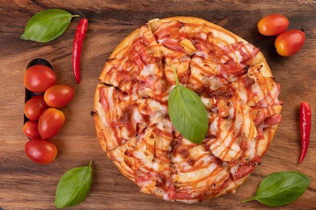 トマトチリとバジルの木製トレイのピザ。