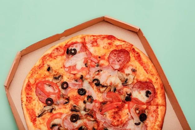 色付きのテーブルの上の茶色の段ボールのテイクアウトボックスのピザ。丸いピザ