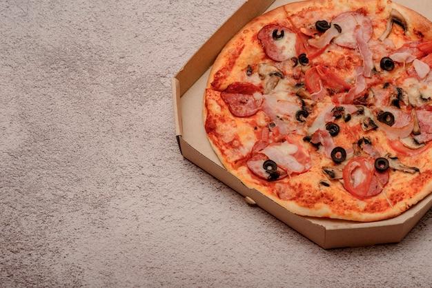 灰色のテーブルの上の茶色の段ボールのテイクアウトボックスのピザ。丸いピザ