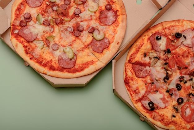 テーブルの上の茶色の段ボールのテイクアウトボックスのピザ。丸いピザ
