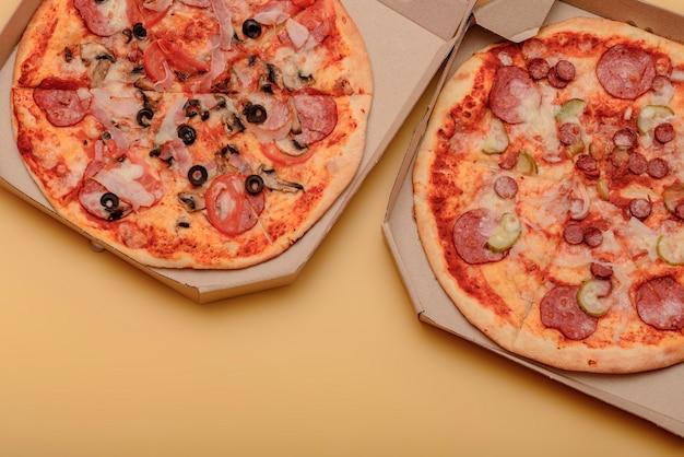 黄色のテーブルの上の茶色の段ボールのテイクアウトボックスのピザ。丸いピザ