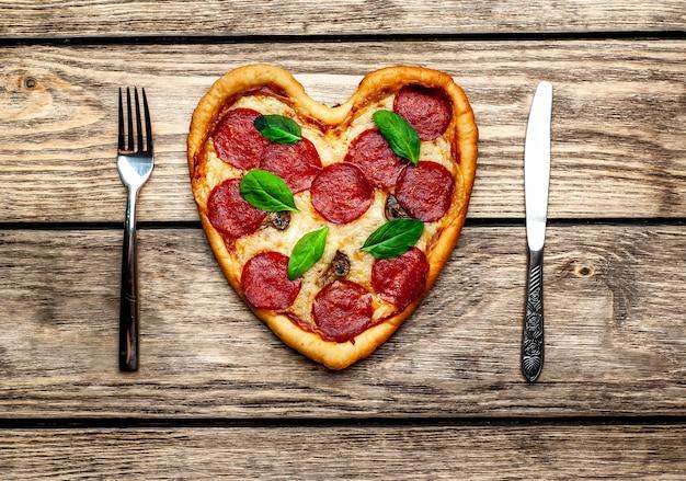 木製のテーブルにハートの形のピザ
