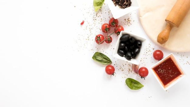 Ингредиент для пиццы с хлебом для пиццы и скалкой на белом фоне