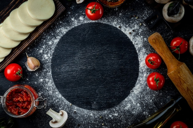 Pizza ingredients on black table