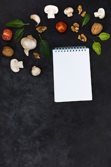 Pizza ingredients over the blank white spiral notepad against black textured background