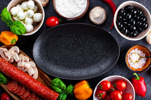 Pizza ingredients on the dark background and black plate. pepperoni sausage, mozzarella cheese, tomatoes, olives, mushrooms and flour are different products for making pizza and pasta.
