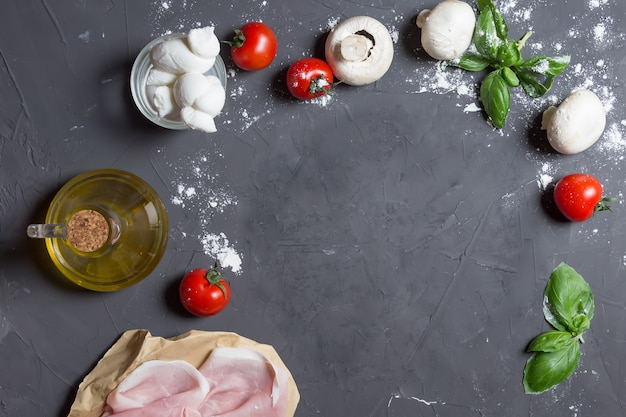 Pizza ingredients on the grey background with copy space at the center, dough, tomatoes, mushrooms, basil, ham