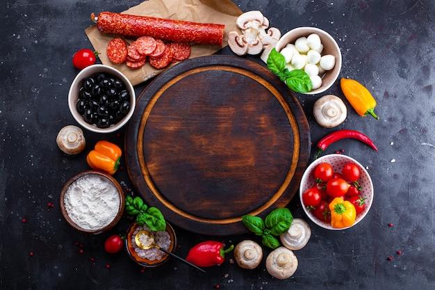 어두운 배경 및 라운드 커팅 보드에 피자 재료. 페퍼로니, 모짜렐라, 토마토, 올리브, 버섯 및 밀가루는 피자와 파스타를 만들기위한 다양한 제품입니다.