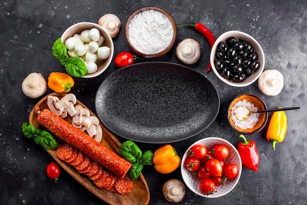 어두운 테이블과 검정 접시에 피자 재료. 페퍼로니 소시지, 모짜렐라 치즈, 토마토, 올리브, 버섯 및 밀가루는 피자와 파스타를 만들기위한 다양한 제품입니다.