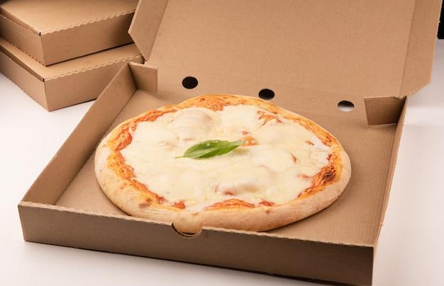 配達ボックスの背の高いスタックのオープンボックス内のピザがクローズアップ