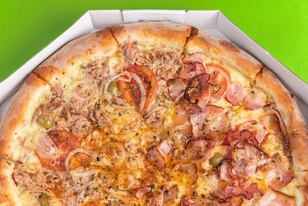Пицца внутри упаковки на зеленом столе