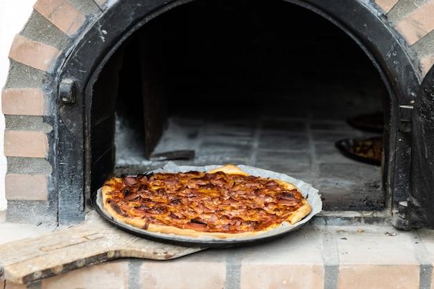 외부에 흰색 페인트를 칠한 장인의 나무 화덕으로 만든 피자