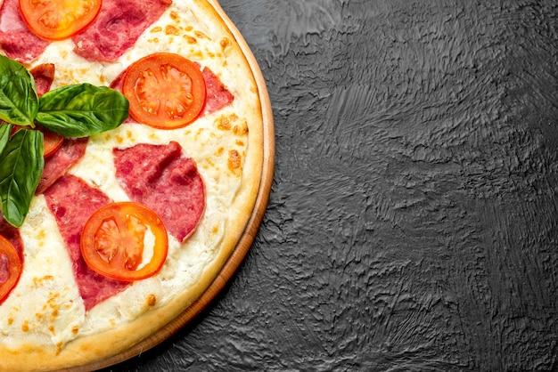 검은색 바탕에 크림 베이스에 모짜렐라 치즈가 어우러진 피자 마르첼로