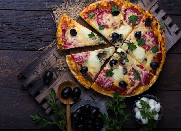 Pizza margarita or margherita with tomatoes, mozzarella cheese and fresh greens. margarita pizza with pizza knife over background on rustic wooden table