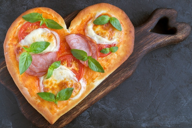 Pizza margarita in the shape of a heart for valentine's day.