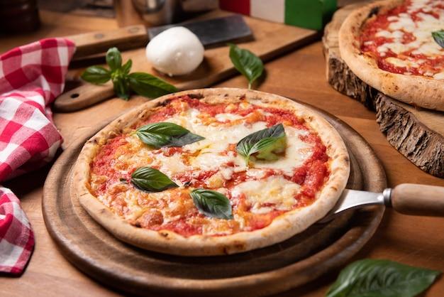 Пицца маргарита со свежими листьями базилика на деревенском столе
