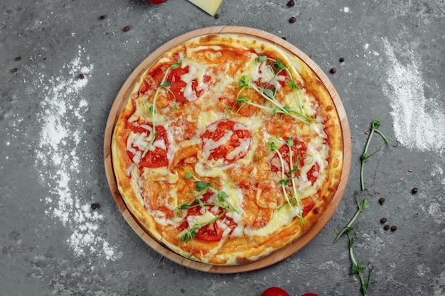 黒い石の背景、上面にピザマルゲリータ。トマト、バジル、モッツァレラチーズのピザマルガリータ