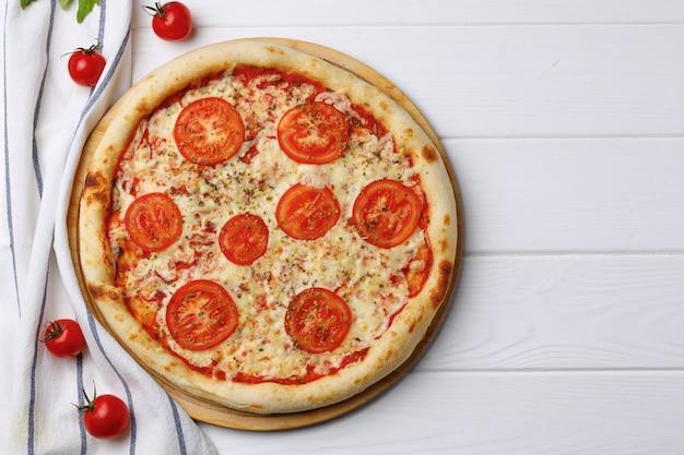 白い木製のテーブルに乗ってピザマルゲリータ