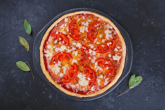 Pizza margherita with cheese and tomatoes on dark