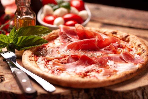 Pizza margherita with parma ham on a rustic table