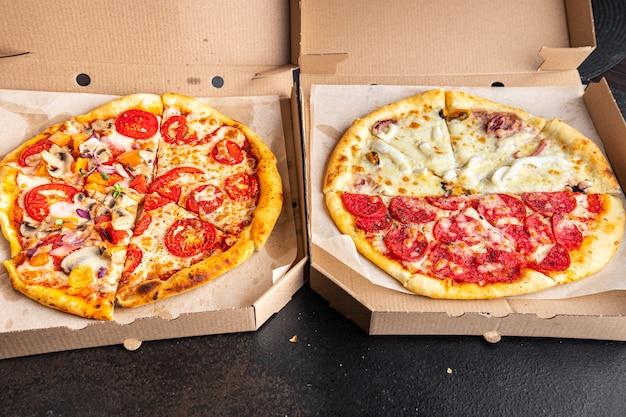 ピザは、テーブルの上で食事の軽食を食べる準備ができている1つの箱の新鮮な部分にさまざまな種類のピザを混ぜます