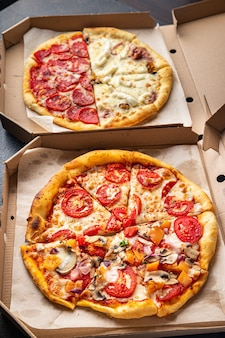 Pizza mix different types of pizza in box fresh fast food ready to eat meal snack on the table