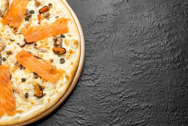 Pizza naples on a black background, cream-based with mozzarella