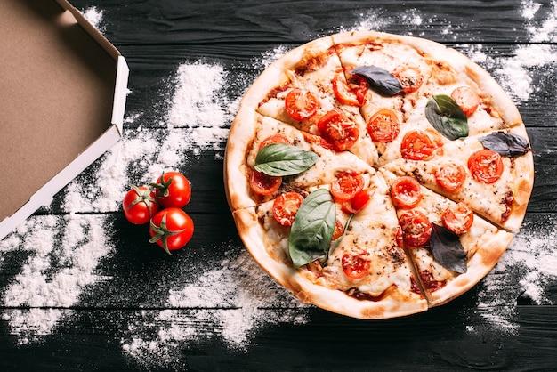 パッケージの横にある黒い木製のテーブルの上のピザ
