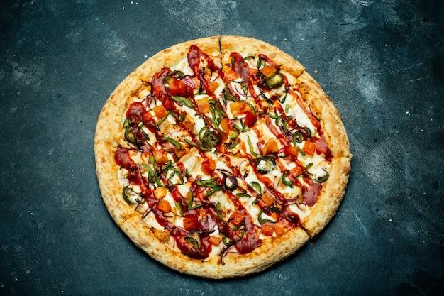 暗い背景にピザ。暗いキッチンテーブルにトマト、コショウ、野菜、ソース、モザレラチーズの古典的なイタリアのピザ。コピースペース