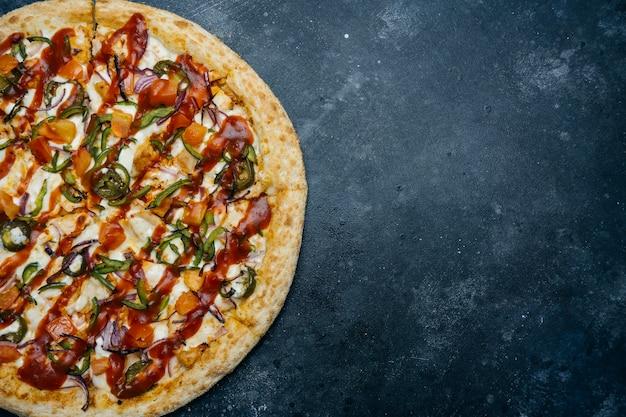 暗い背景にピザ。暗いキッチンテーブルにトマト、コショウ、野菜、ソース、モザレラチーズの古典的なイタリアのピザ。